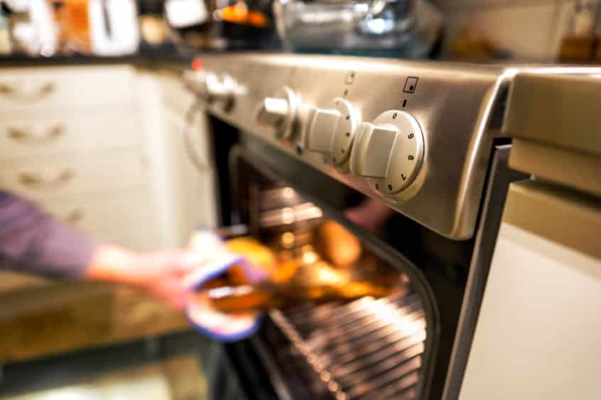 Hand of person taking out hot dish from elecrtic oven in kitchen